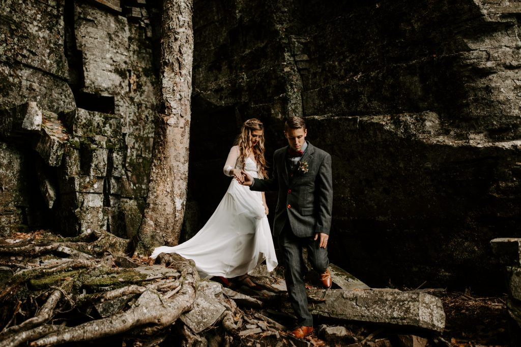 Bride and groom exploring Michigan's waterfalls after their elopement